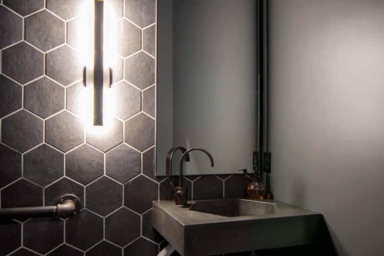 Black hexagon shaped concrete sink and hexagon wall tiles