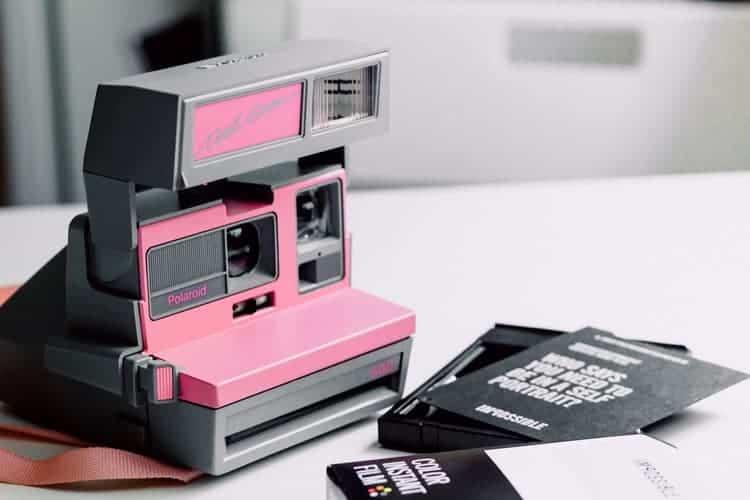 polaroid camera with film on white table