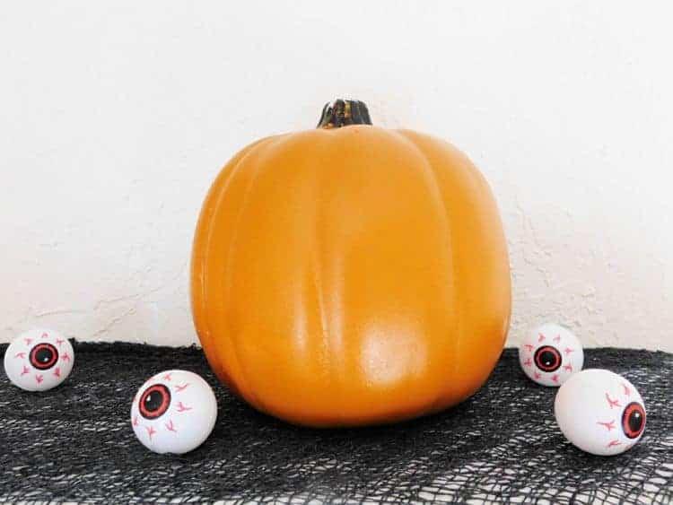 Fake pumpkin on black fabric with little eyeballs on display