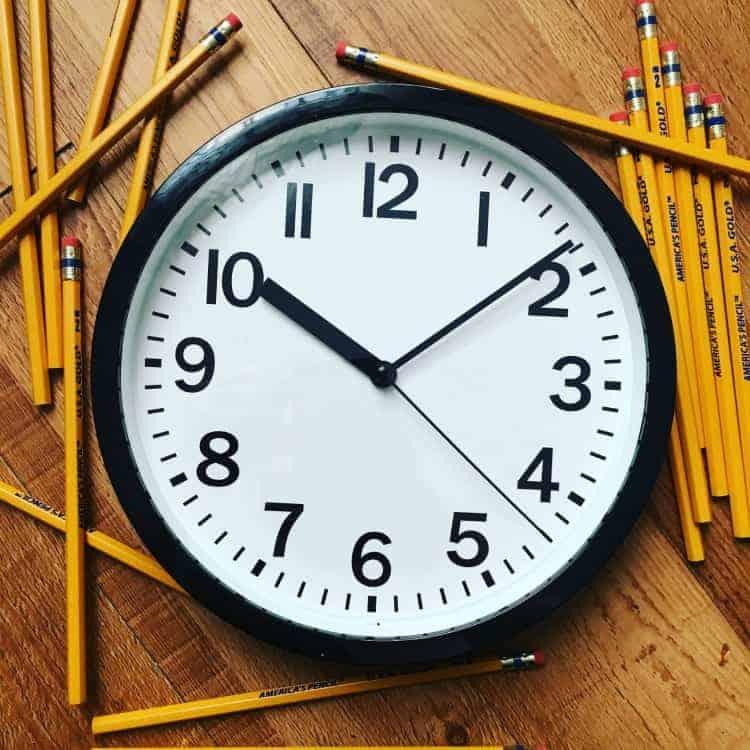 school clock with pencils around it