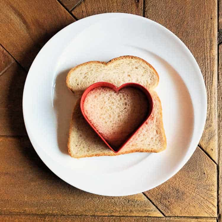 using the heart shaped cookie cutter to cut out a heart of the bread