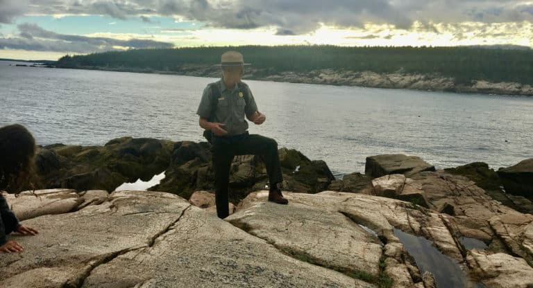 A national park ranger explains acadia's geology from atop some of its coastal boulders.