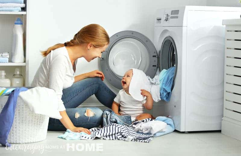 mom with a baby engaged in laundry fold clothes into the washing machine