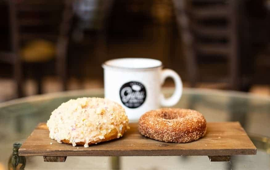two donuts on a board in front of a cup of coffee
