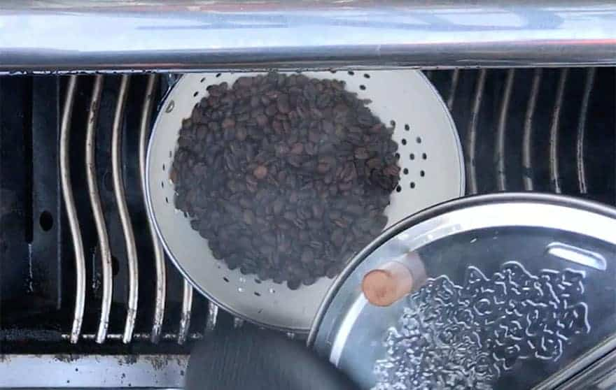 Dumping hot roasted coffee beans into a colander to cool