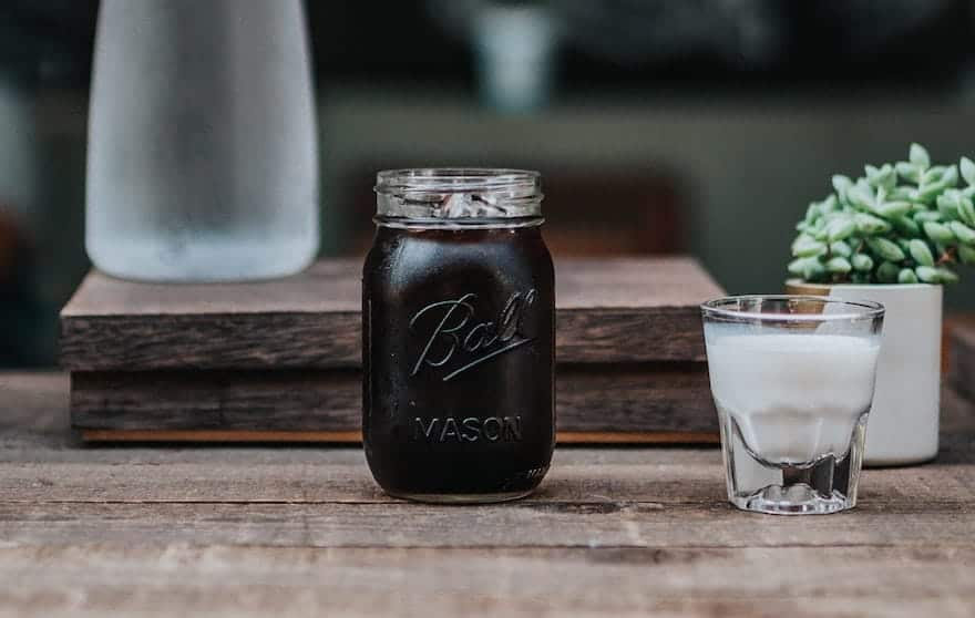 Cold brew coffee in a mason jar with a side of cream