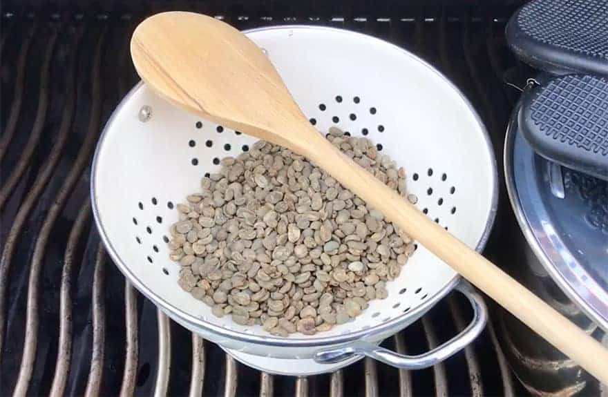 Raw green coffee beans in a colander on the barbecue grill