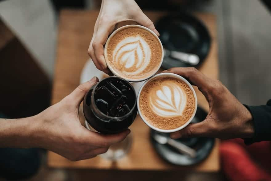 Three hands clinking coffee beverages