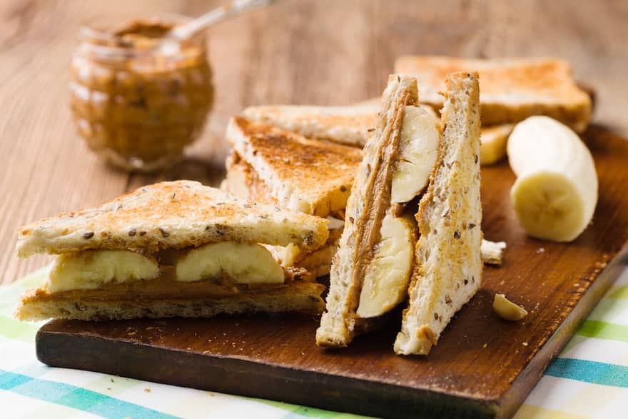 Peanut butter and banana sandwiches cut into triangles on a cutting board