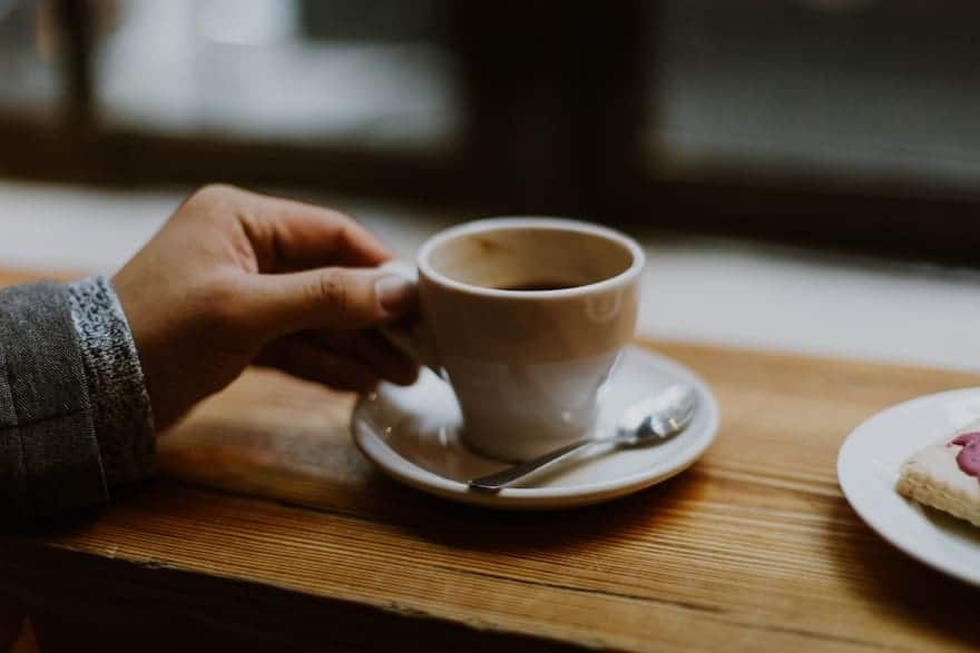 hand grasping an Americano cup