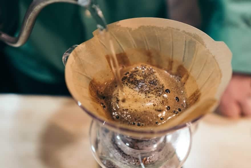 Closeup of water being poured onto the grounds in a Hario V60 coffee brewer