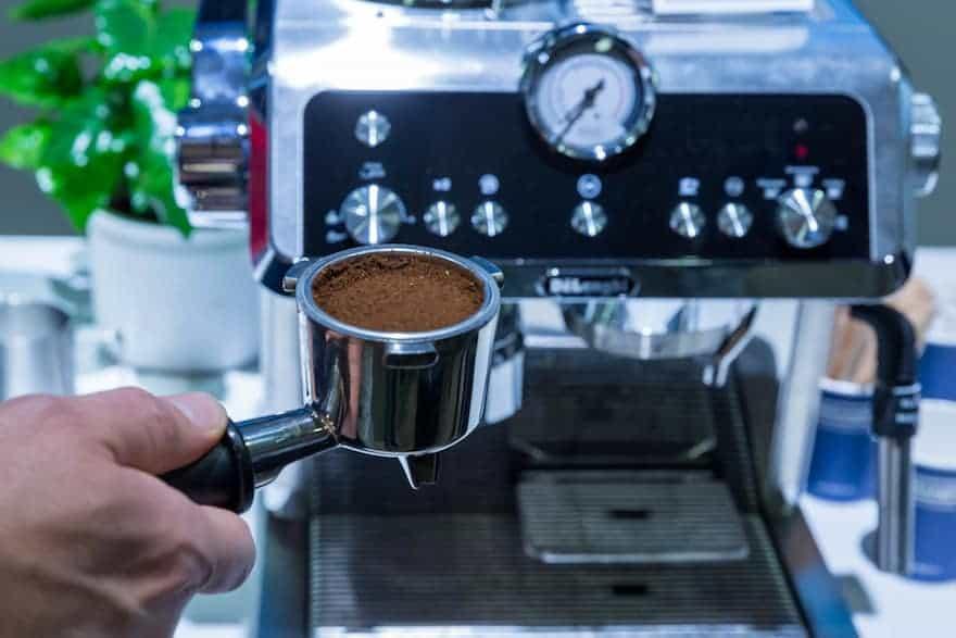 Hand holding ground coffee in a portafilter in front of a De'Longhi La Specialista espresso machine
