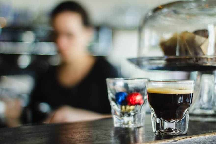 Long espresso on a bar with a barista in the background