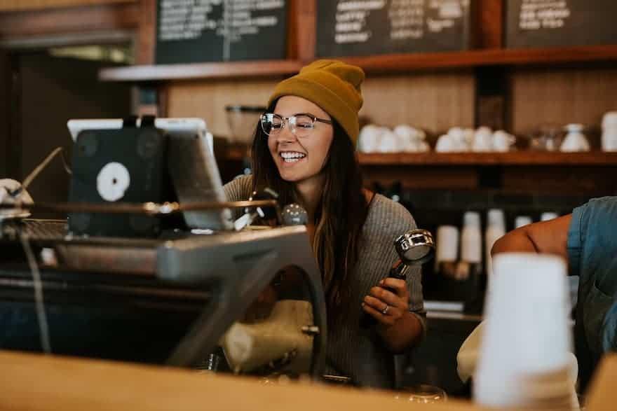 Smiling female barista behind an espresso machine in a coffee shop