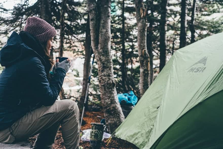 Woman drinking coffee next to a tent while camping