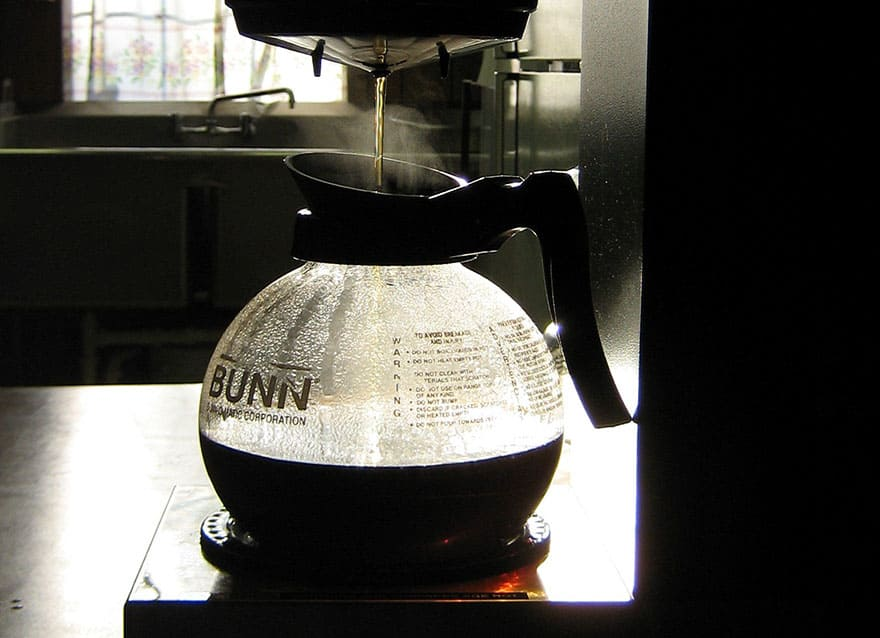 Coffee brewing in a Bunn coffee maker in a sunny kitchen