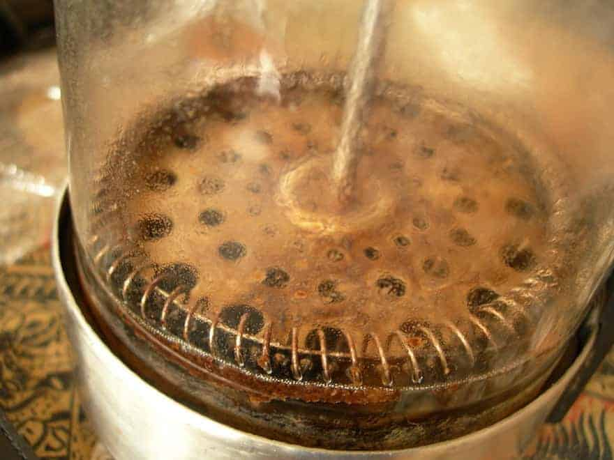 Coffee grounds and sludge at the bottom of a French press after brewing