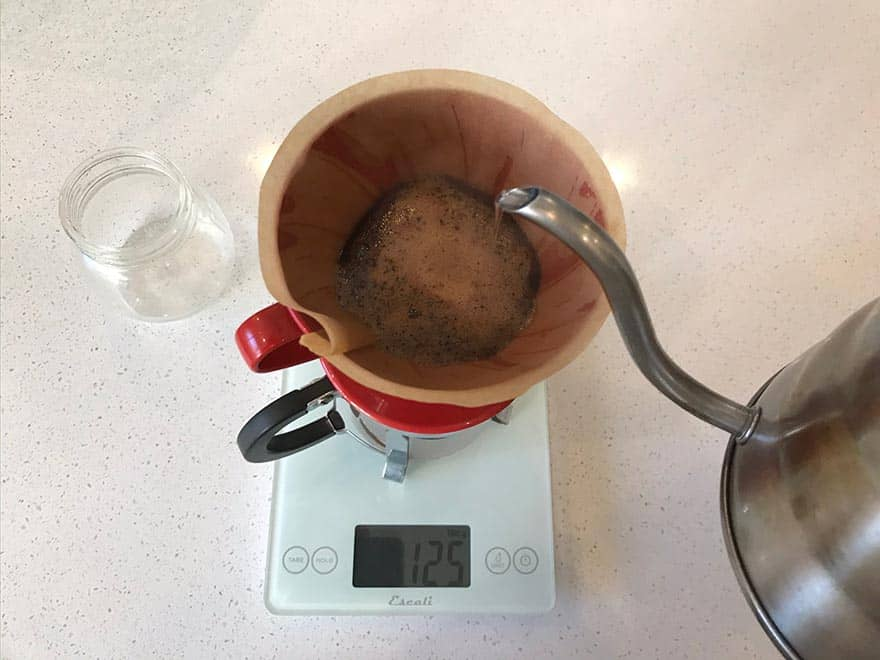 Coffee brewing in a Hario V60 pour-over cone on top of a scale.