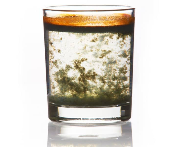 35512691 - toxic water. glass filled with dirty water with a yellow-green precipitate