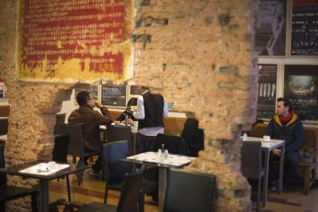 Patrons sip coffee at a cafe in Beijing's Arts district