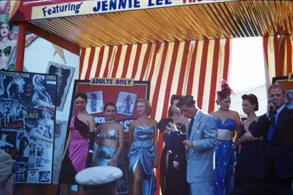 Photo of bally for Jennie Lee's show at the Canadian National Exhibition, 1956. Image shows several female performers lined up next to a collage of images of Jennie Lee. A red striped tent wall is visible behind them. To the right is the show's talker, a man in a blue suit with a microphone. In the foreground, a man in a military cap looks on.