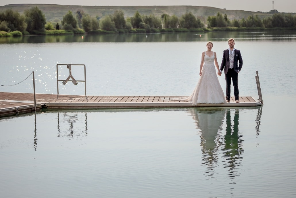 Brautpaar auf einem Steg am Wasser