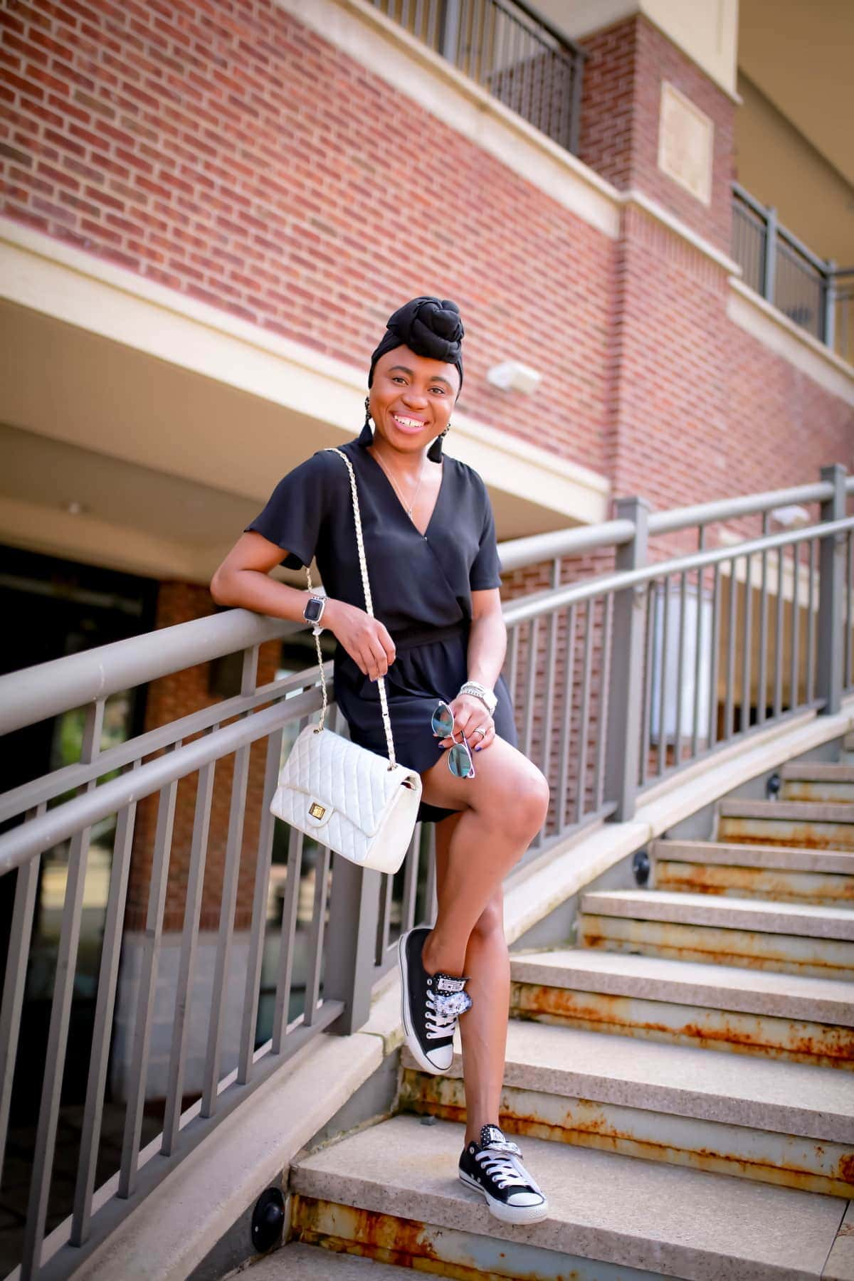 2 of 3 ways to style a black dressy romper. For a practical everyday look, style your romper with a pair of sneakers like she did here. A quilted structured bag for texture and a beautiful lightweight chandelier earrings and retro reflective sunnies for the get-work-done appeak. #everydaystyle #casualwomensfashion #blackoutfit