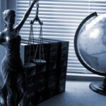 A table with lady justice statue, along with a globe, and some books