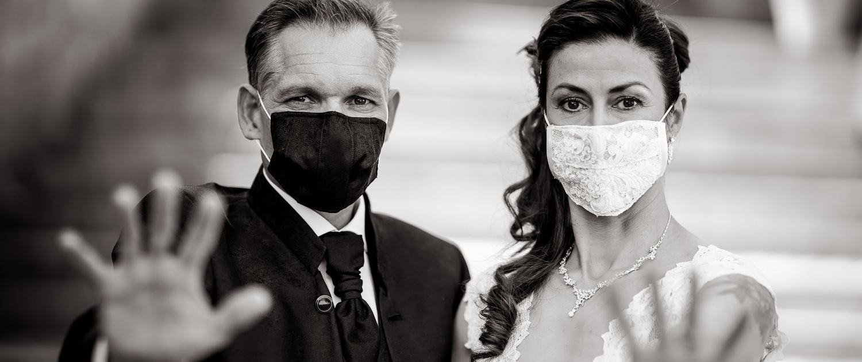 Braut & Bräutigam tragen einen Mundschutz und halten die Hände abwehrend Richtung Kamera Canon EOS R & RF 85mm