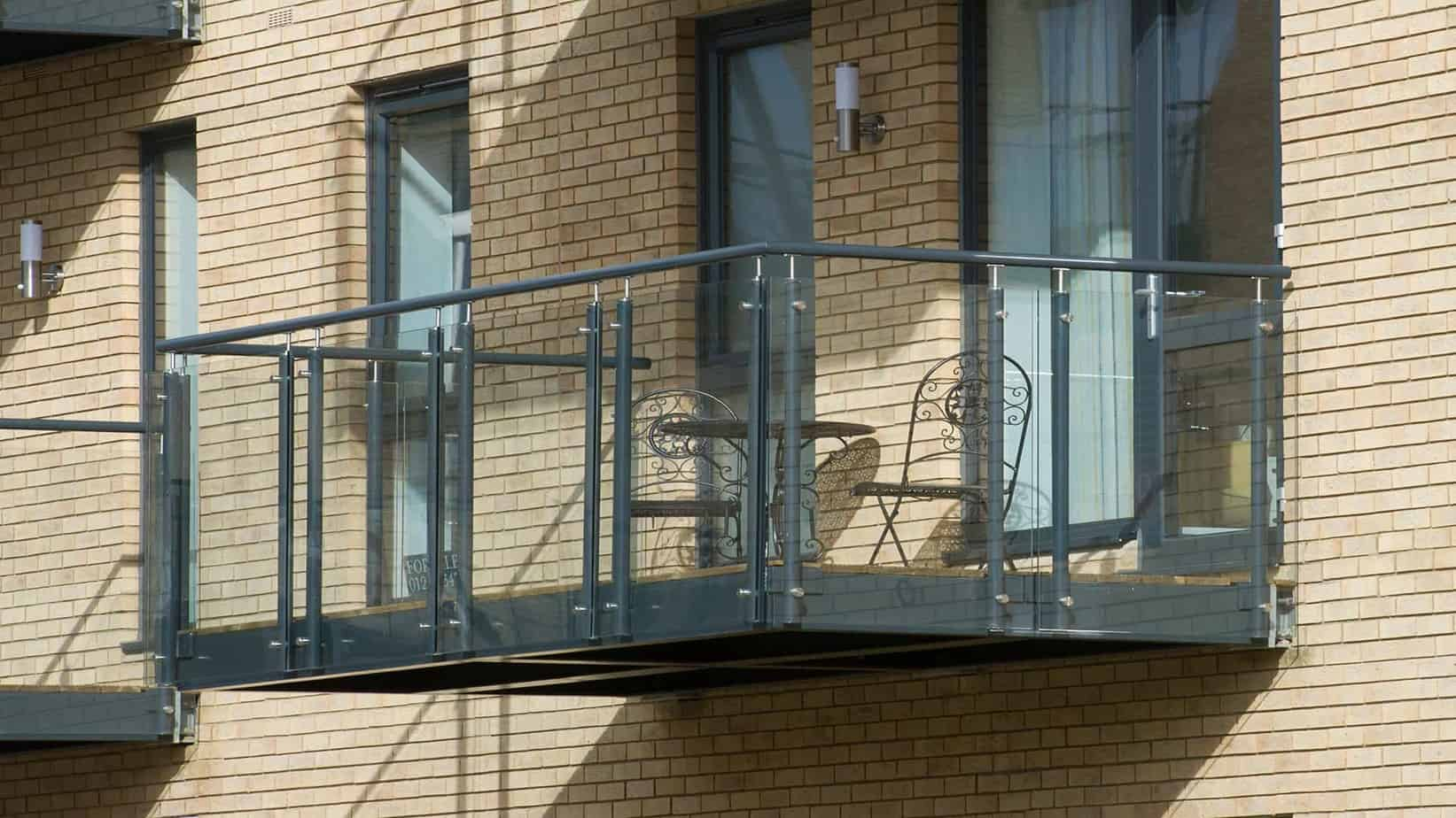 View of the green and a table and chairs on the balcony from the Tailored Stays DeHavilland House serviced apartment near Addenbrookes hospital