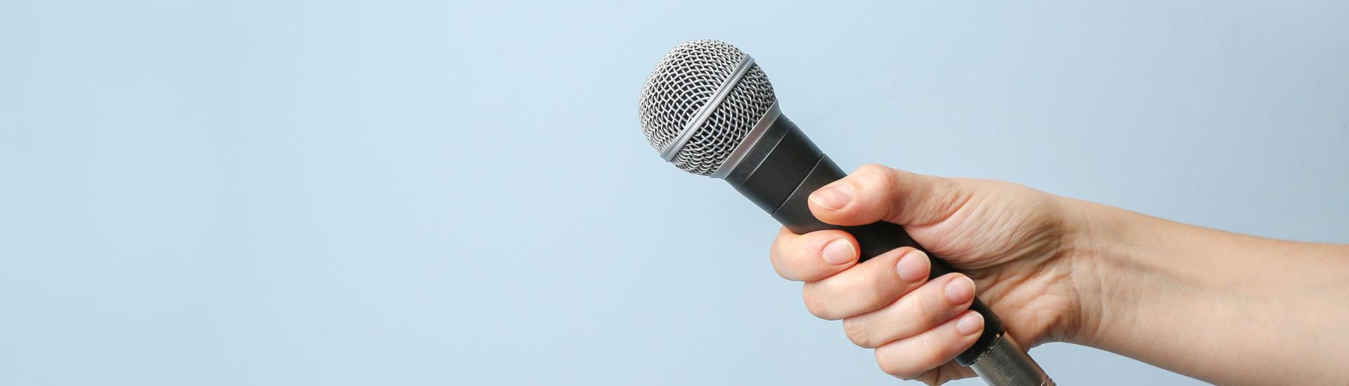 Hand hält Mikrofon vor blauem Hintergrund