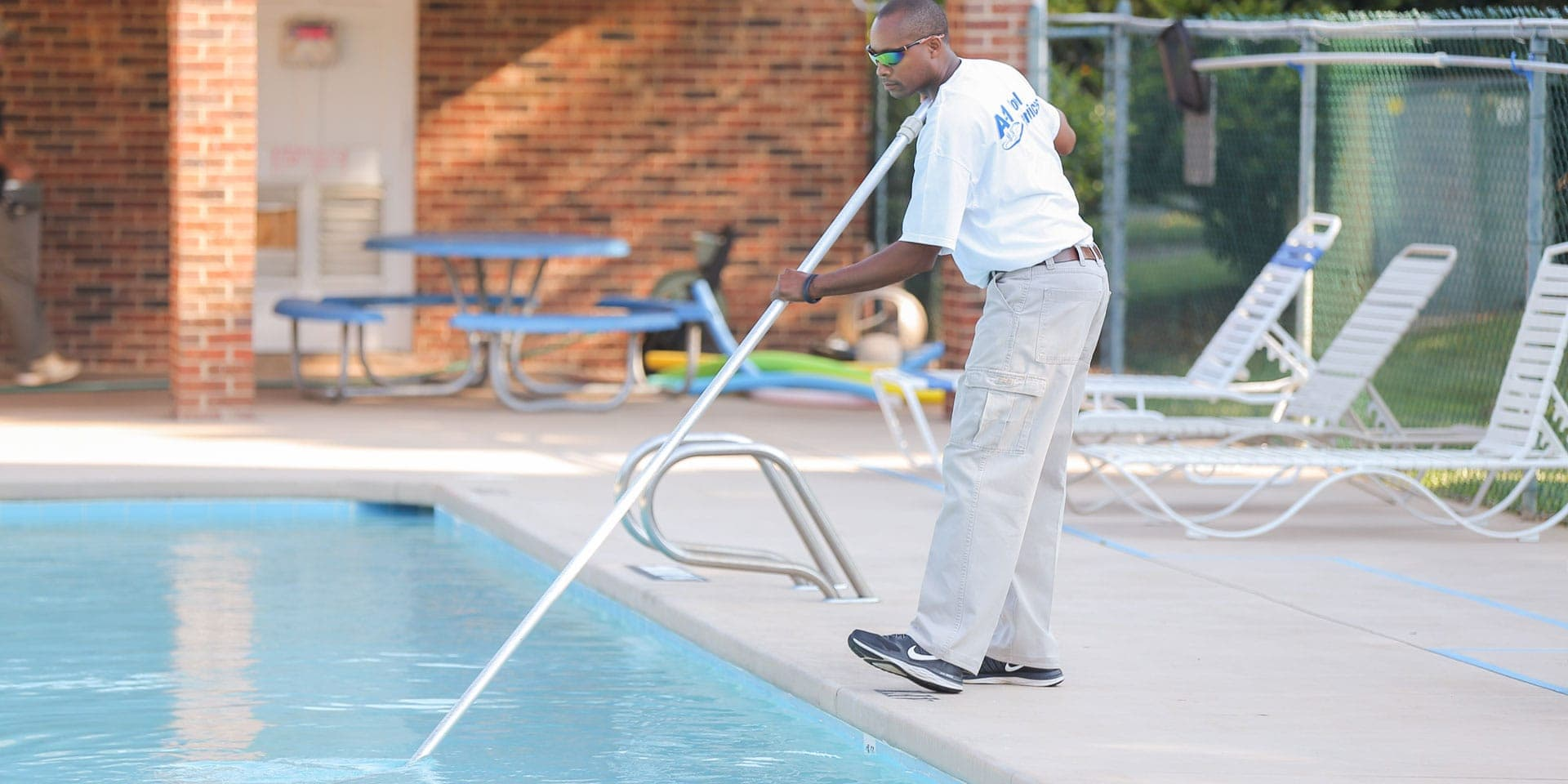 man cleaning up pool as part of pool maintenance