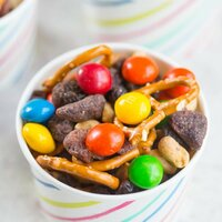 Close up of Peanut Butter and Jelly Trail Mix in small white cardboard bowl with colored stripes