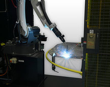 Image of robotic MIG gun welding with sparks