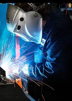Welder welding with a Bernard GMAW gun as sparks fly