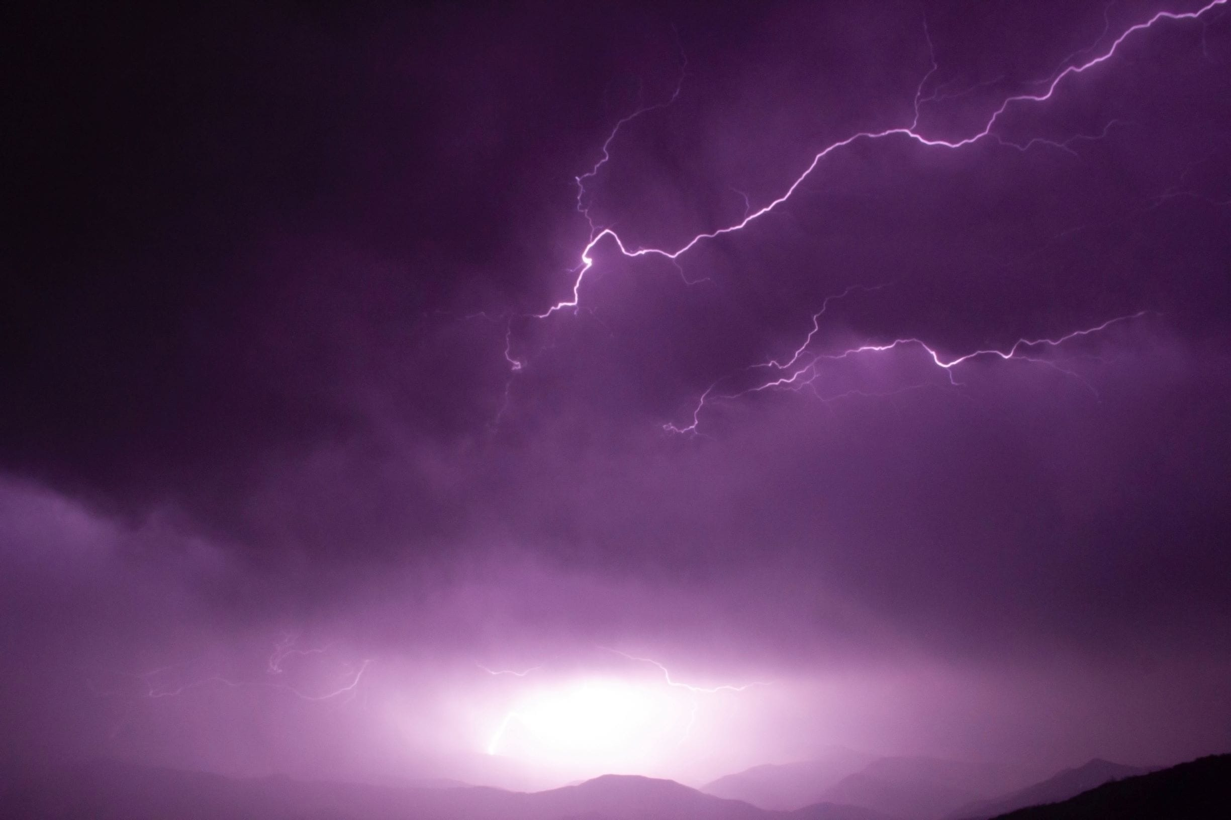 purple storm clouds and lightning over mountains