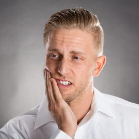 man rubbing jaw because of tooth pain