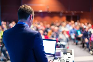 Speaker,At,Business,Conference,And,Presentation.,Audience,At,The,Conference