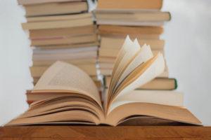 aufgeschlagenes Buch vor einem Bücherstapel