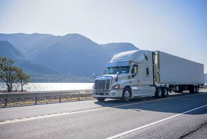 White tractor trailer on road next to lake and mountains