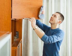 man cleaning wooden furniture