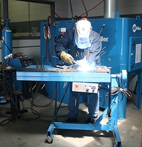 Image that shows person welding in a proper ergonomic setting on the plant floor