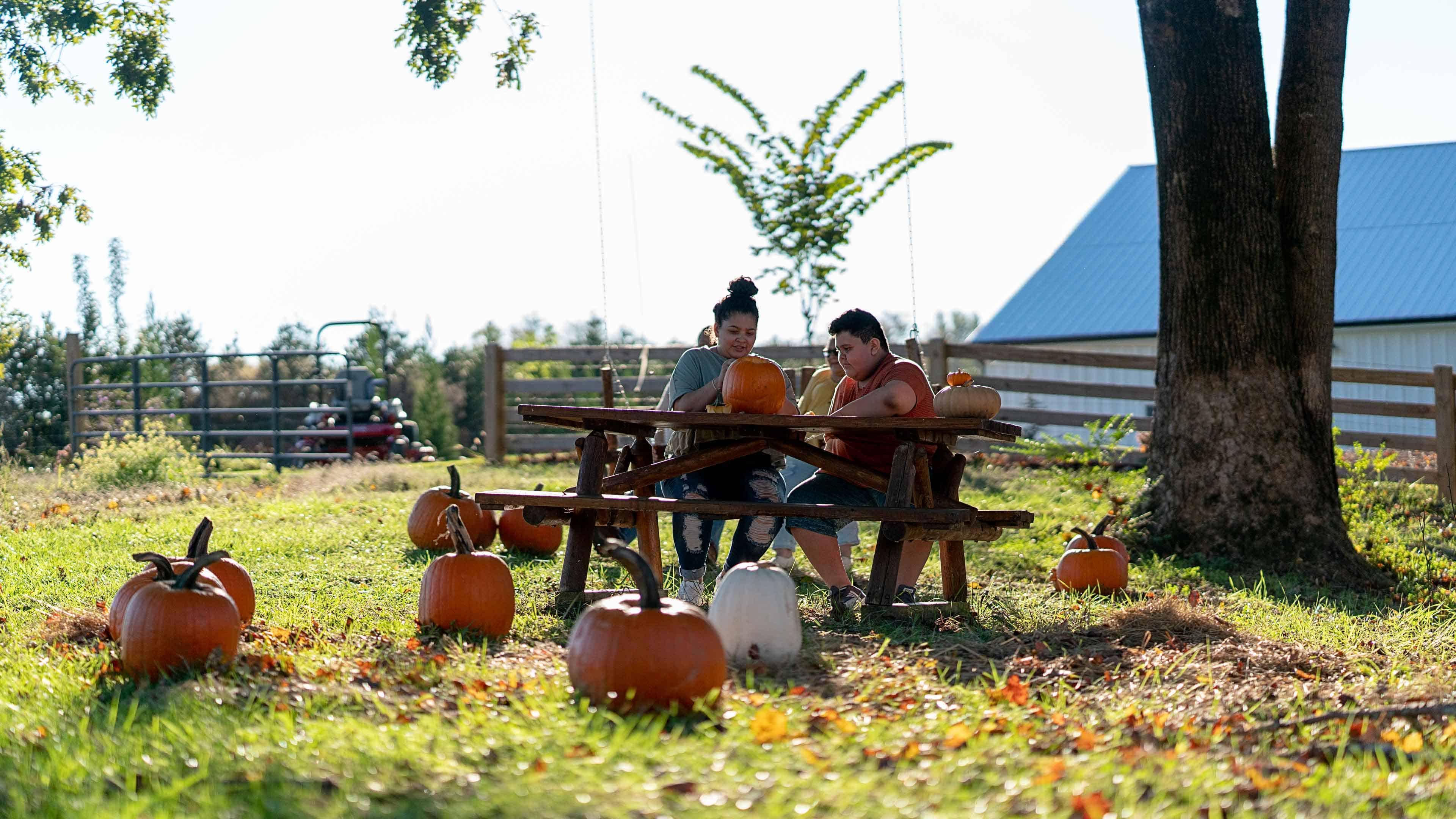rural children sitting at a picnic table making jack o'lanterns