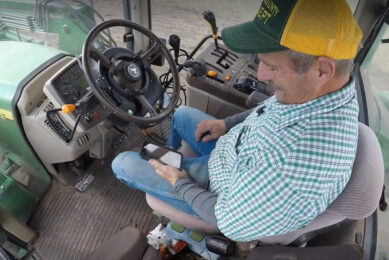 Farmer checking his smartphone whilst his tractor is driving partially autonomously thanks to AgJunction autosteer. - Photo: Still from AgJunction video