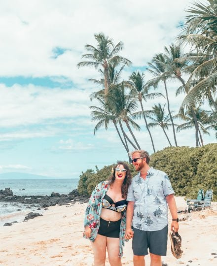 Couple laughing and holding hands on the beach in Maui, Hawaii