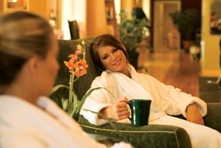 two women relaxing at the spa in robes drinking tea
