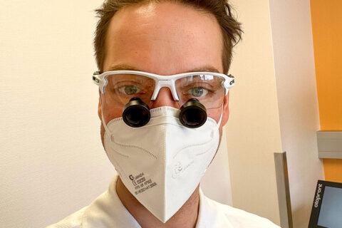 HNO-Arzt OA Dr. Philipp Wimmer mit einer Lupenbrille in seiner HNO-Ordination in 1100 Wien, direkt neben der Therme Wien