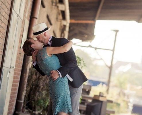 Hochzeitspaar küsst sich innig auf einer alten Laderampe, eins der coolsten Hochzeitsshootings des vergangenen Jahres...