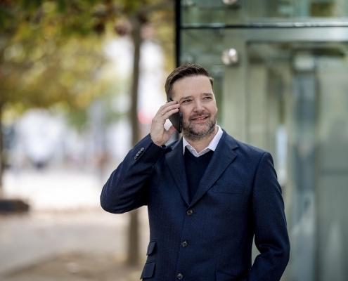Geschäftsmann in lockerer Haltung beim telefonieren fotografiert mit der Canon EOSR6 & RF 85mm f/1.2L USM in Erfurt