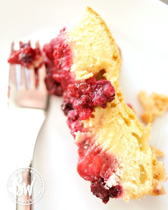 A beautiful slice of summer fruit sponge pudding with a layer of yellow sponge and chunky berries.